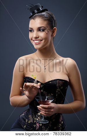 Smiling woman posing in fancy dress and little hat, stirring cocktail glass handheld.