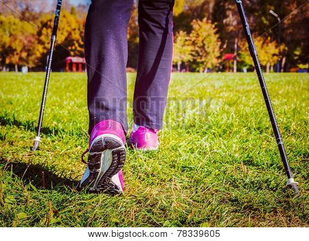 Vintage retro effect filtered hipster style image of nordic walking adventure and exercising concept - woman hiking, legs and nordic walking poles in summer nature