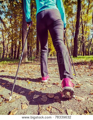 Vintage retro effect filtered hipster style image of nordic walking adventure and exercising concept - woman hiking withnordic walking poles in park