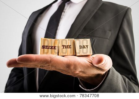 Businessman Holding Wooden Cubes In The Palm Of His Hand With The Words Seize The Day