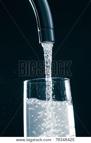 pouring a glass of water from mixer tap
