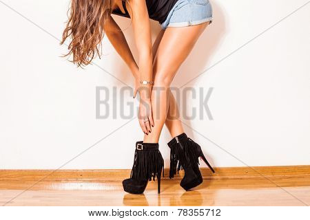 fashion girl in high heel shoes jeans shorts and black top tank stand on parquet against wall in room