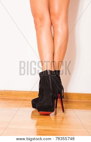 woman legs in black high heels ankle boots on parquet against wall