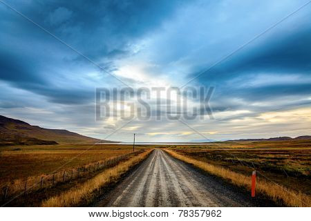 Straight gravel road through the fields in Northwestern Iceland