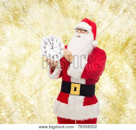 christmas, holidays, time and people concept - man in costume of santa claus with clock showing twelve pointing finger over yellow lights background