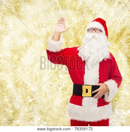 christmas, holidays, gesture and people concept - man in costume of santa claus waving hand over yellow lights background