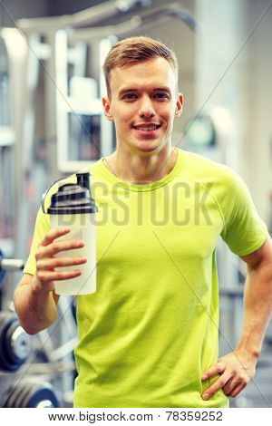 sport, fitness, lifestyle and people concept - smiling man with protein shake bottle in gym