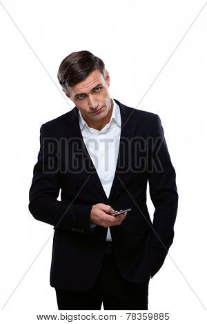 Serious businessman standing with smartphone over white background