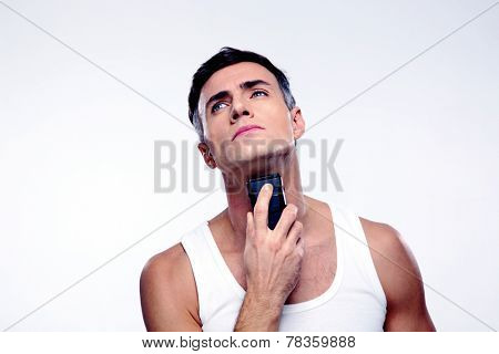 Confident man shaving with electric razor over gray background