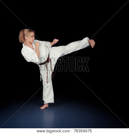 Young Karate Woman in a White Kimono Kicking