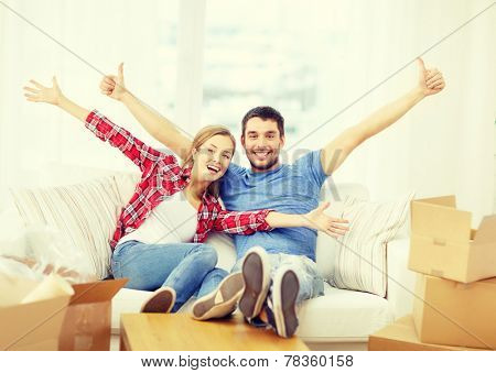 moving, home and couple concept - smiling couple relaxing on sofa in new home