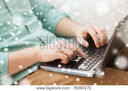 technology, home, people and lifestyle concept - close up of man working with laptop computer and sitting on sofa at home