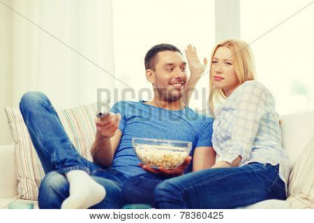 food, love, family and happiness concept - smiling couple with popcorn choosing what to watch at home