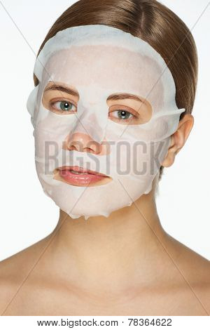 Portrait of beautiful young woman applying rejuvenation facial mask on her face