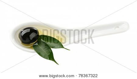 Sauce spoon with oil and a black olive with leaves isolated on white