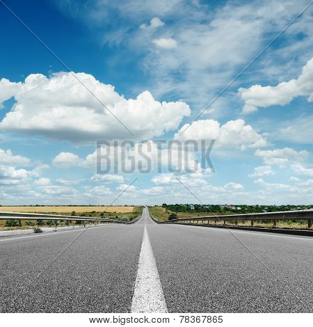 asphalt road with white line on center close up under cloudy sky