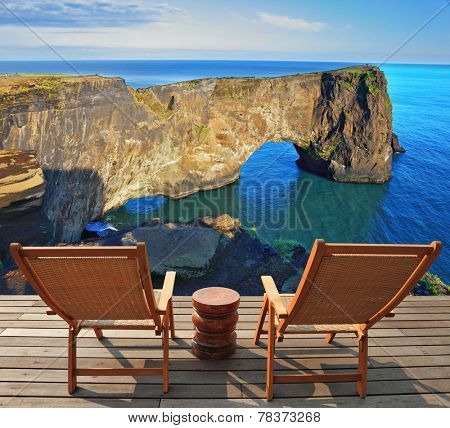 Cape Dirholaey in southern Iceland in July. On a coastal rock delivered comfortable wooden loungers.  The colossal rock lit summer sunset