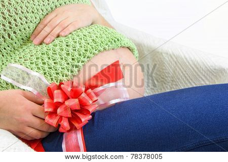 Pregnant Woman's Cute Belly With Big Red Ribbon