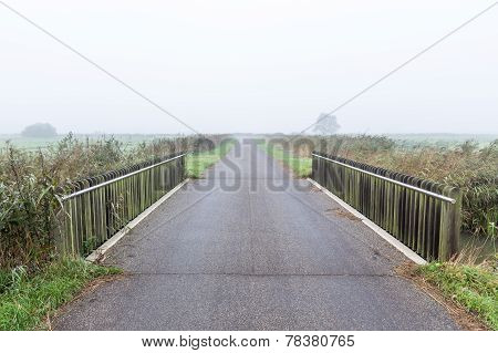 Bridge Over Water In A Misty Morning Rural Landscape In The Netherlands