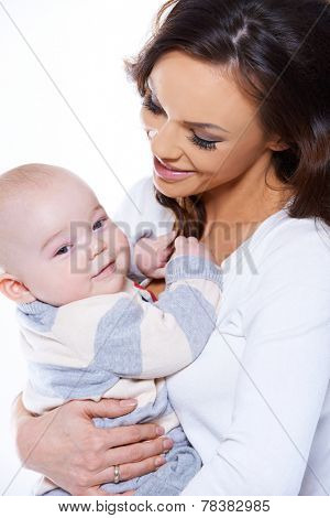Loving mother cradling her happy baby son in her arms as the infant turns to look at the camera with a beaming smile