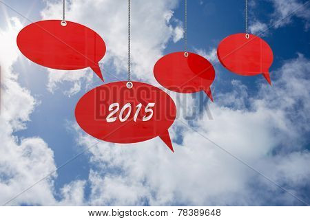 2015 speech bubble tags against bright blue sky with clouds