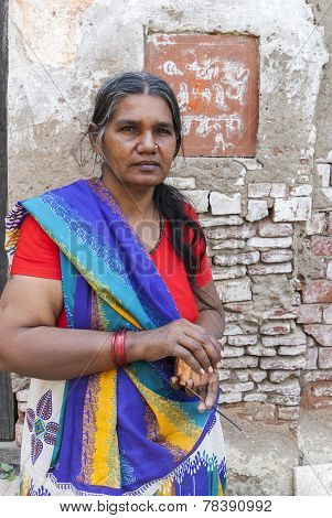Graying Woman In Colorful Sari Holds Incense Stick.