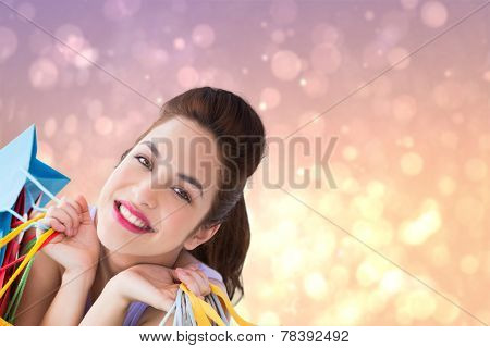 Portrait of a happy brunette holding shopping bags against pink abstract light spot design