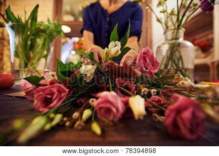 Female florist sorting fresh flowers in workshop