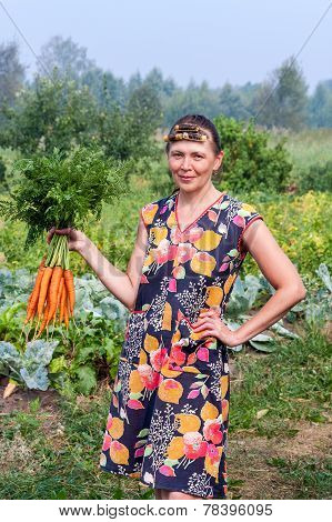 Young Woman Holding A Large Bundle Of Carrots