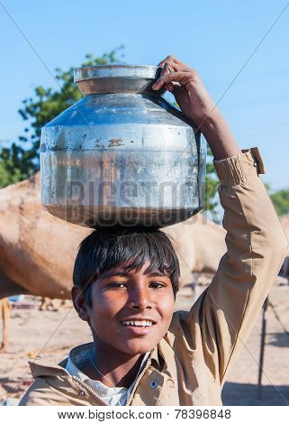 Young Boy With Metal Pot Of Water On His Head.
