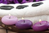 pic of swedish sauna  - black hotstones on white towel with purple candles - JPG