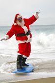Постер, плакат: Surfing Santa Claus Santa Claus rides on his surfboard as he rides the waves of the ocean blue San
