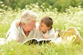 stock photo of grandfather  - Grandfather and his grandson reading book outdoor - JPG