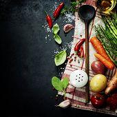 foto of tablespoon  - Wooden spoon and ingredients on dark background - JPG