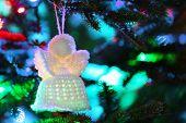 stock photo of christmas angel  - Knitted Christmas angel on Christmas lights background - JPG