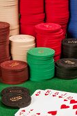 foto of flush  - Photo of a royal flush of hearts in front of stacks of gambling chips - JPG