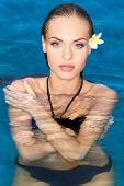 picture of chest hair  - Exotic gorgeous young woman with frangipani in her hair standing chest high in the water in the swimming pool looking at the camera with a sensual expression - JPG
