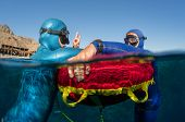 pic of split ends  - Split shot of two free divers training in sea with buoy - JPG