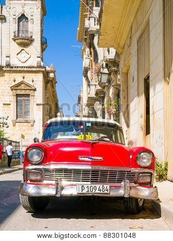 HAVANA, CUBA - APRIL 15,2015 : Vintage red car on a narrow street on the colonial neighborhood of Havana