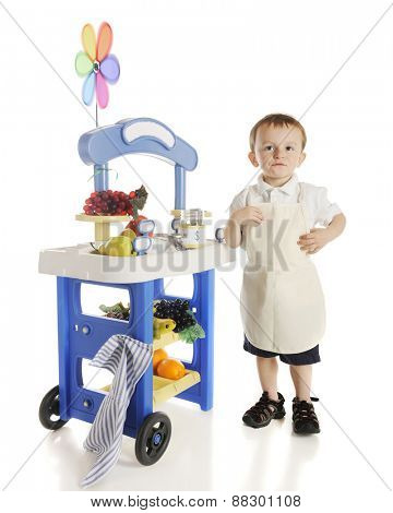 A preschool vendor standing by his fruit stand.  The stand's signs are left f blank for your text.  On a white background.
