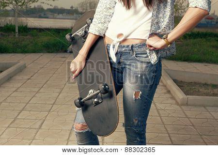 Fashion portrait of female holding a skateboard, closeup