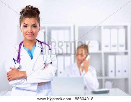 Portrait of young woman doctor with white coat standing