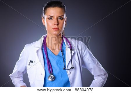 Young doctor woman with stethoscope isolated on grey background
