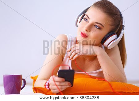 Young woman lying on floor and listen to music .