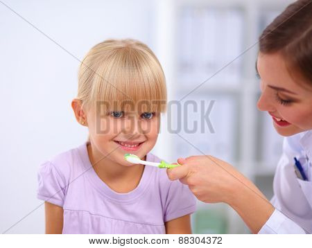 Dentist and little girl in the dentist office .