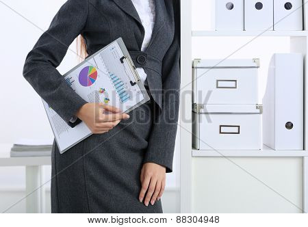 Young happy businesswoman in office holding  folder
