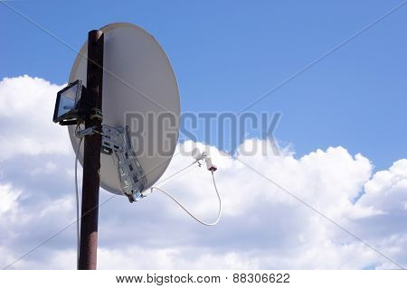 Tv Satellite Dish Mounted On A Stake In Sky
