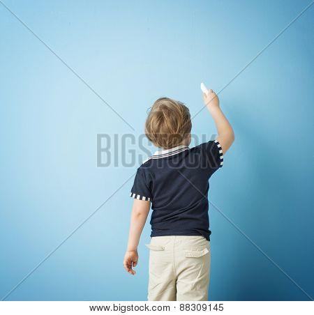 Boy drawing on blank chalkboard