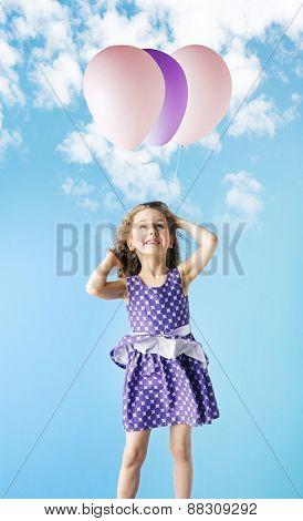 Little girl holding balloons