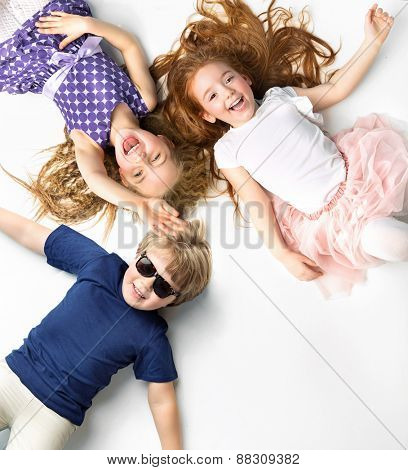 Happy kids lying on white background